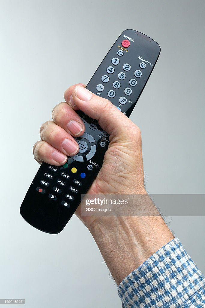 Man holding a TV remote control : Stock Photo