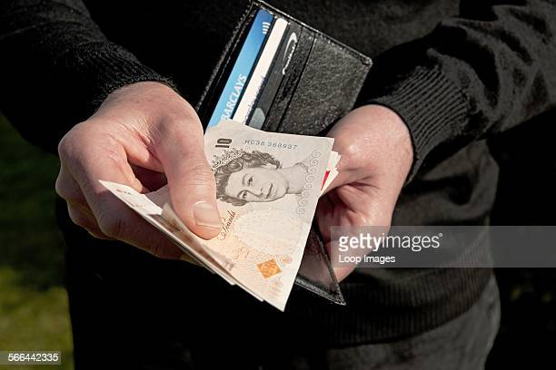 A man holding a wallet and ten pound notes