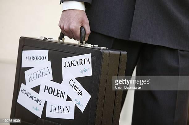 Man holding an attache case with the names of Marokko Korea HongKong Poland Japan China Jakarta Symbol businessman on the run outsourcing