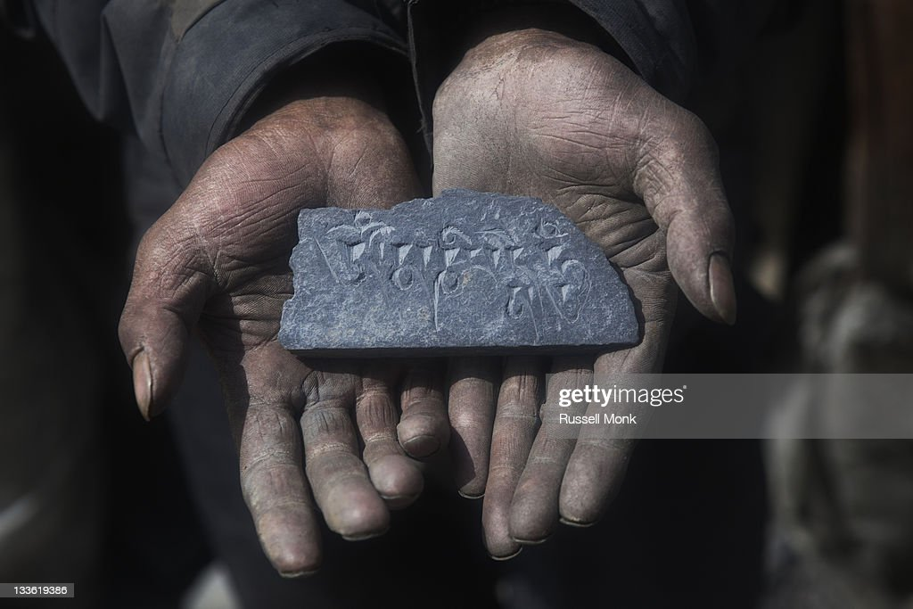 A man holding an engraved stone : Stock Photo
