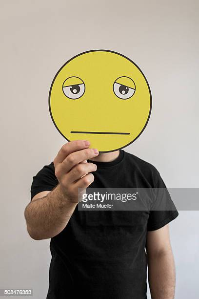 Man holding an exhausted emoticon face in front of his face