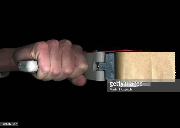 Man holding an industrial tape dispenser