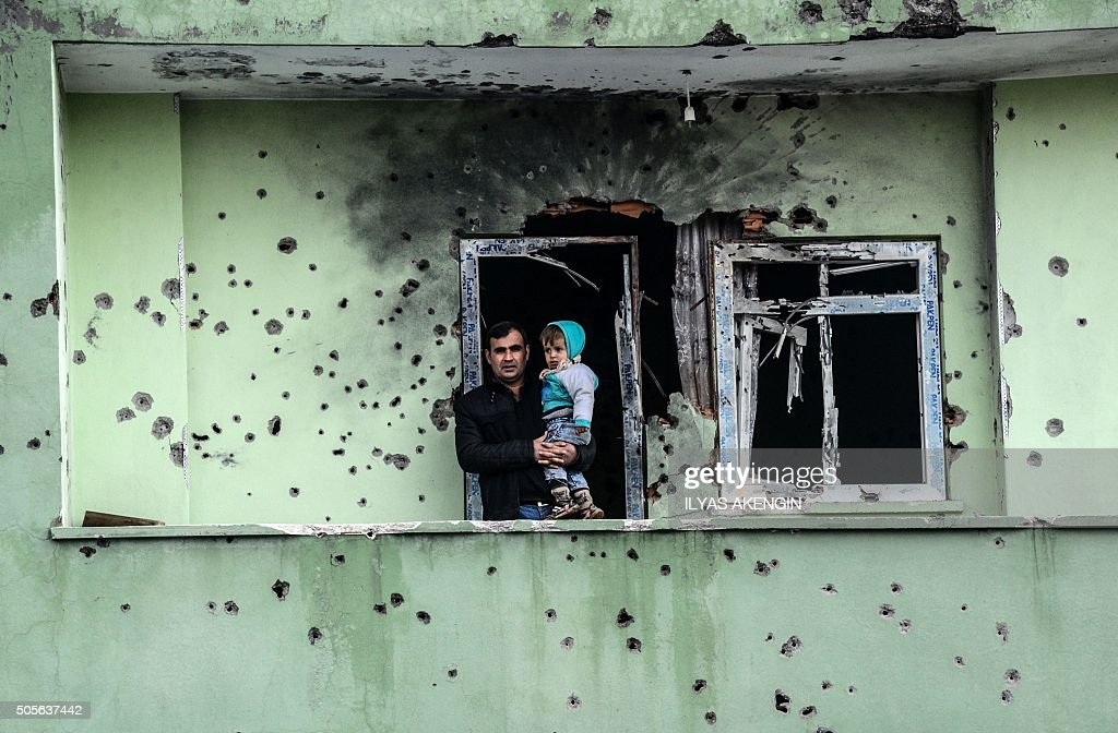 TOPSHOT A man holding an infant stands on the balcony of a damaged house after curfew ended in the southeastern Turkish town of Silopi on January 19...
