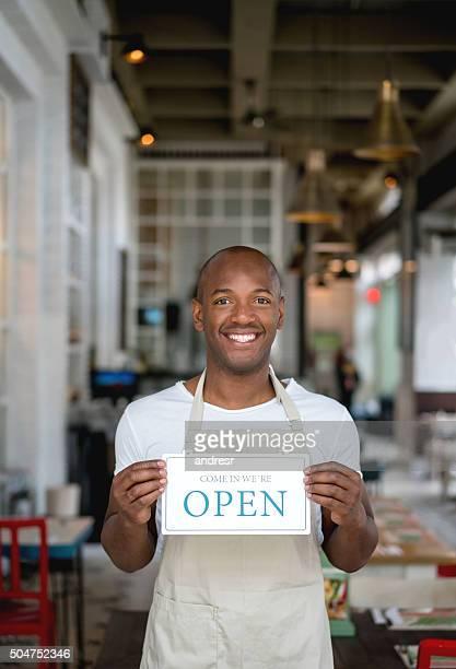 Man holding an open sign outside a restaurant