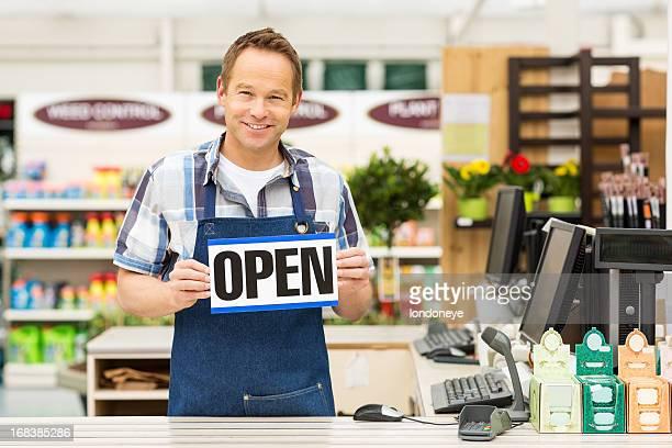 Man Holding an Open Signboard