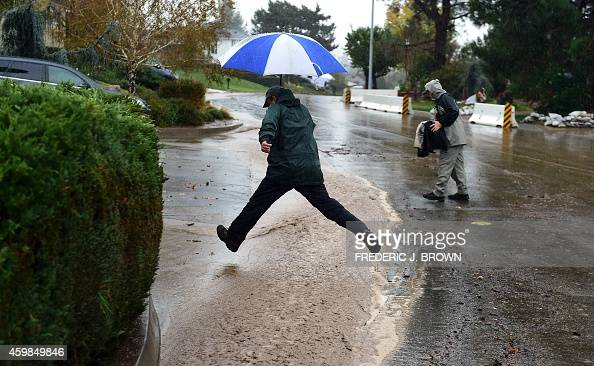 A man holding an umbrella leaps across a channel of running water flowing down Rainbow Drive in Glendora California on December 2 amid a steady and...