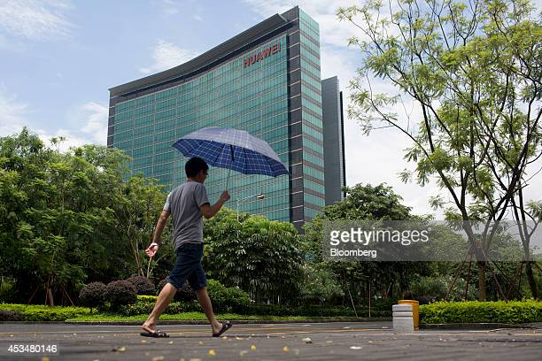 A man holding an umbrella walks past a building at the Huawei Technologies Co campus in the Longgang district of Shenzhen China on Wednesday Aug 6...