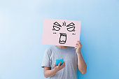 man holding angry expression billboard and take phone  isolated on blue background