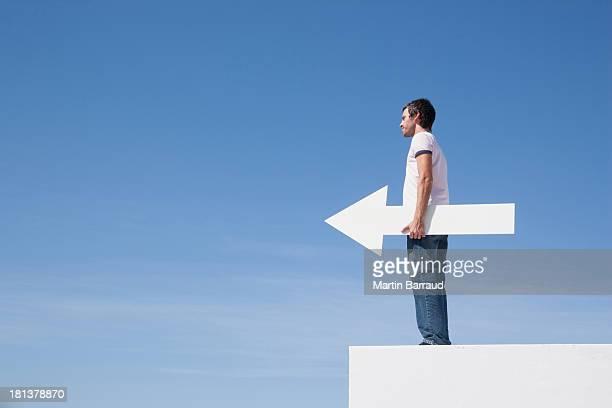 Uomo che tiene la freccia su piedistallo all'aperto