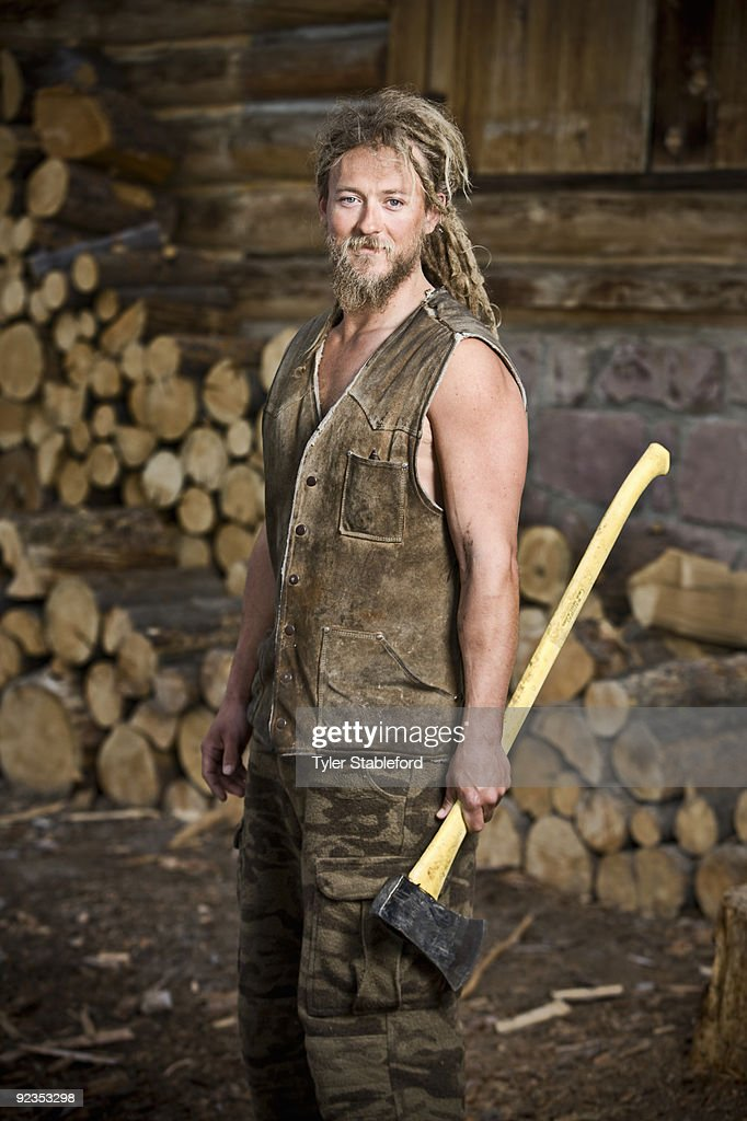 Man holding ax in front of wood pile.