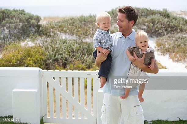 Homem a segurar bebés em ao ar livre