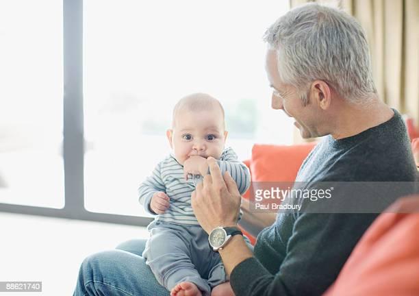 Man holding baby boy on lap