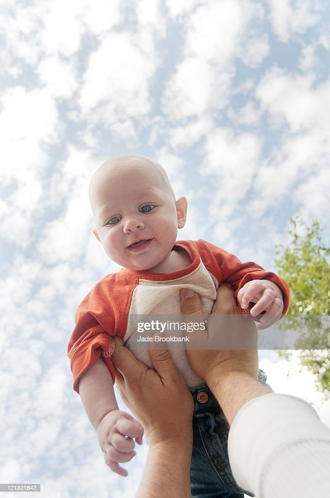 Man holding baby in air : Stock Photo