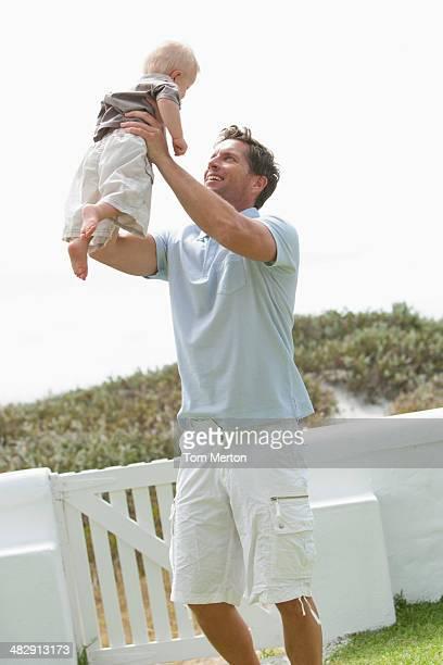 Homem segurando bebê no exterior