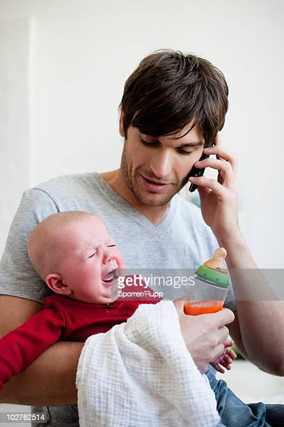 Man holding baby while phoning