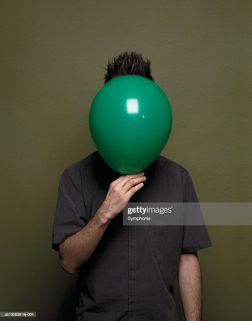 Man holding balloon up to face : Stock Photo