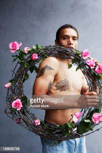 Man holding barbed wire wrapped in roses. : Stock Photo