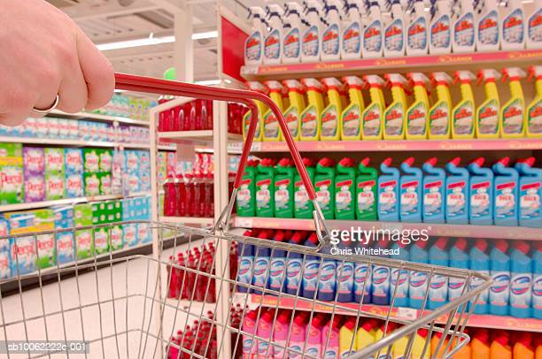 Man holding basket by colourful detergents in supermarket