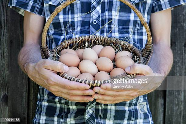 Mann hält Korb voller Eier