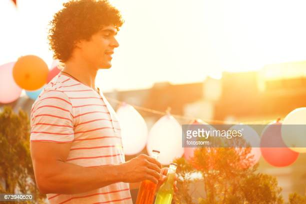 Man holding beer bottles on rooftop