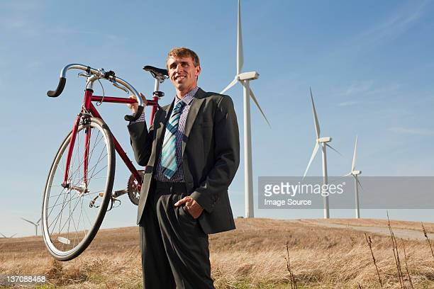 Mann hält Fahrrad vor wind Turbinen