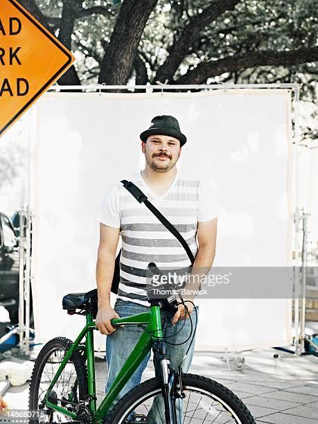 Man holding bicycle on street smiling