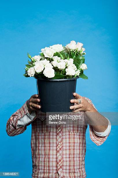 Man holding black bucket of flowers in front of his face