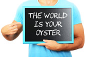 Man holding blackboard in hands and pointing the word THE WORLD IS YOUR OYSTER