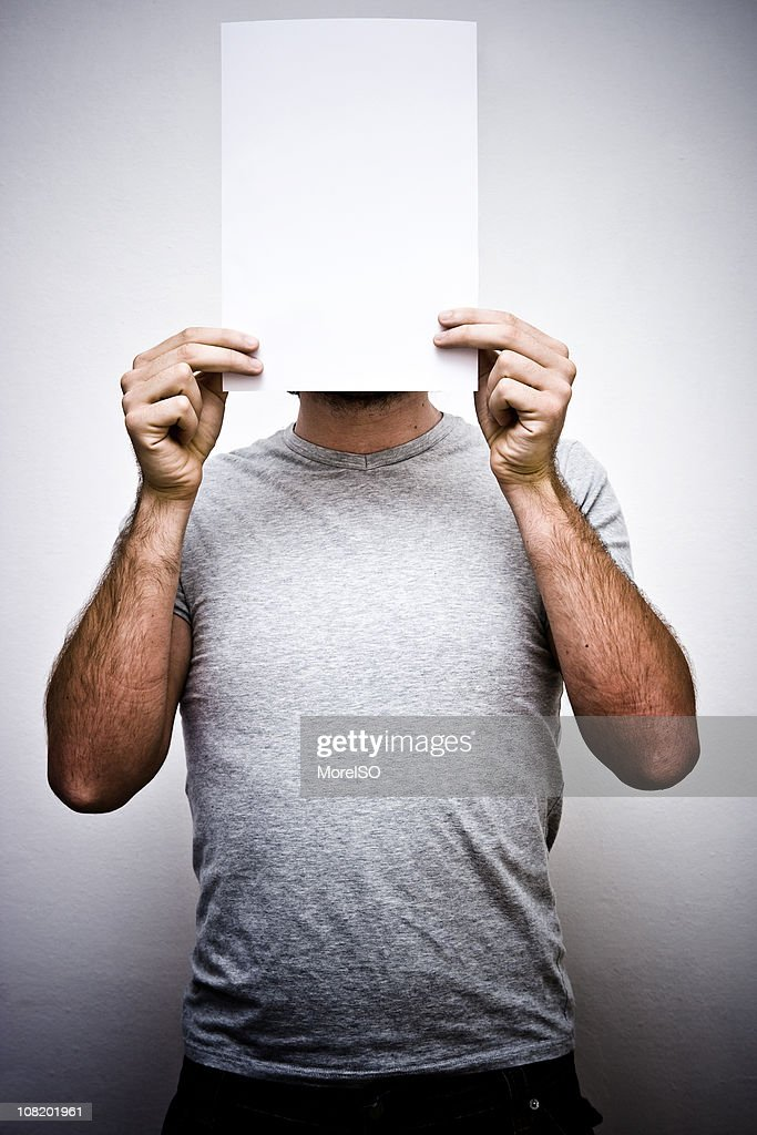 Man Holding Blank Sheet Paper in Front of Face : Stock Photo