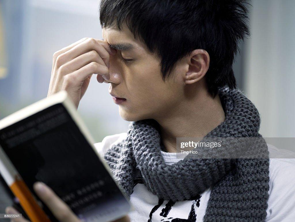 Man holding book, rubbing eyes : Stock Photo