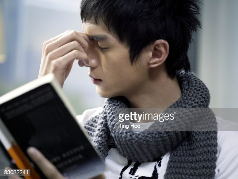 Man holding book, rubbing eyes : Stock Photo