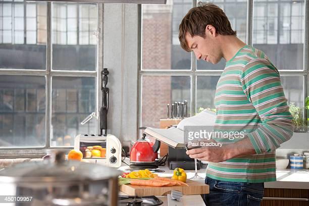 Mann hält Sie bei einem Glas Wein in der Küche