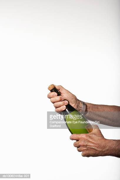 Man holding bottle of champagne with cork ready to pop, close-up of hands
