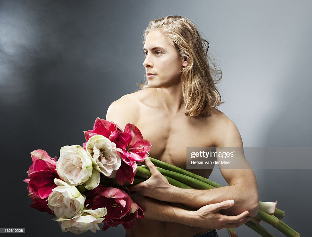 Man holding bouquet of amaryllis flowers. : Stock Photo