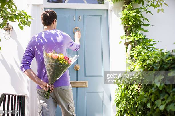 Man holding bouquet of flowers and knocking on door