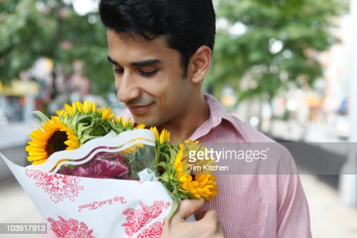 Man holding bouquet of flowers in city, smiling : Stock Photo