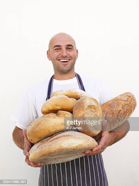 Man holding bread, smiling, portrait