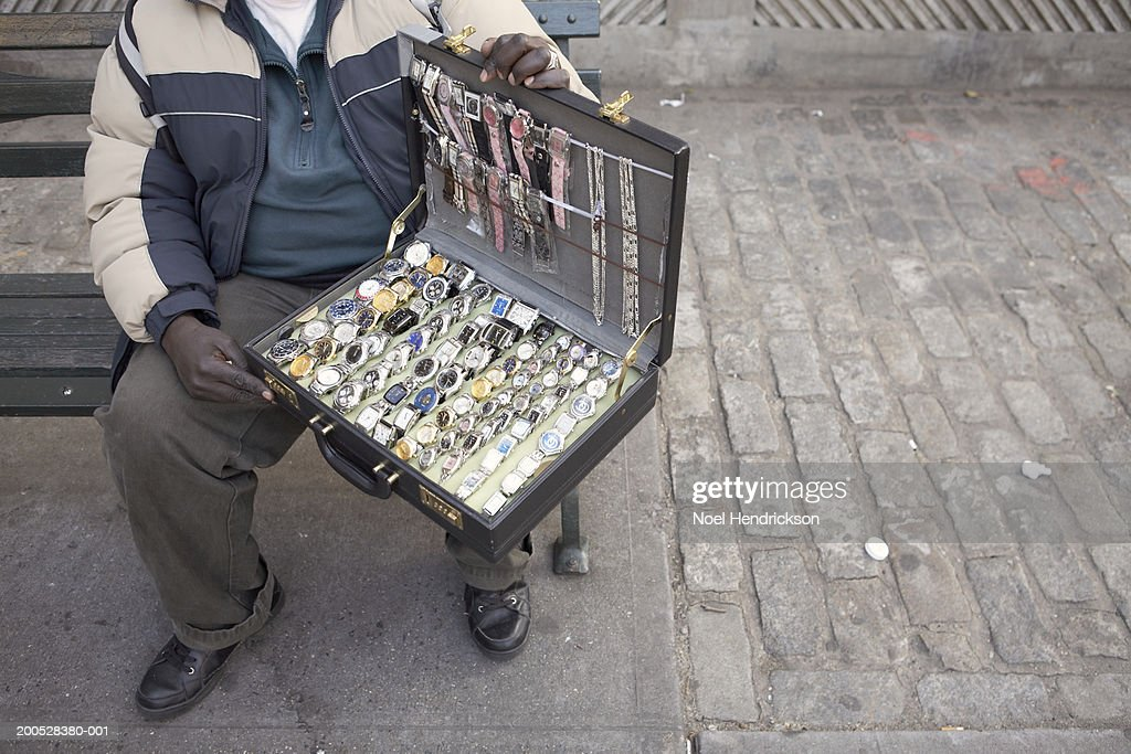 Man holding briefcase of watches on street, low section : Stock Photo