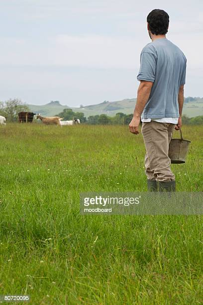 Man holding bucket in field rear view