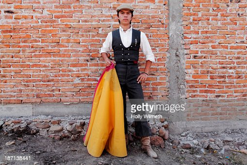 Man holding bullfighting cape in front of brick wall