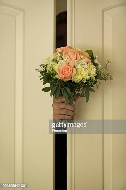 Man holding bunch of flowers through gap in door of house