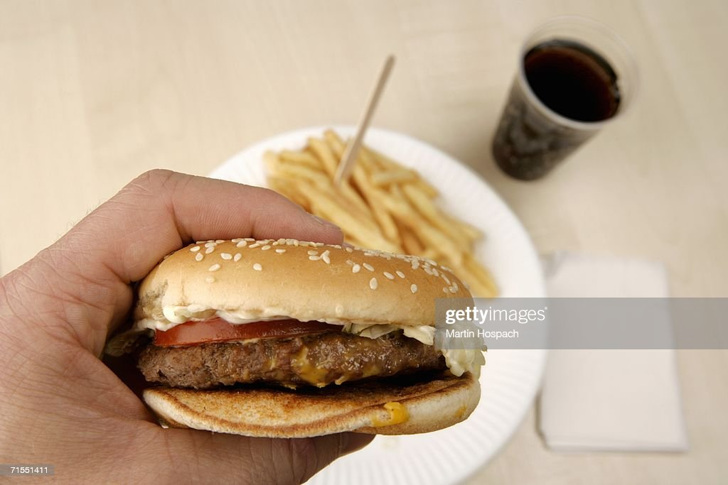 Man holding burger above french fries and cup of cola : Stock Photo