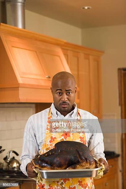 Man holding burned turkey
