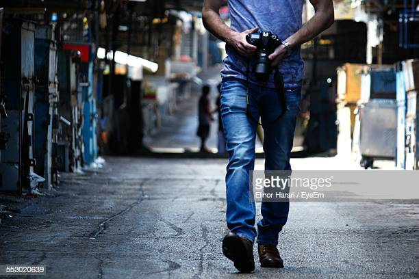Man Holding Camera And Walking In Street