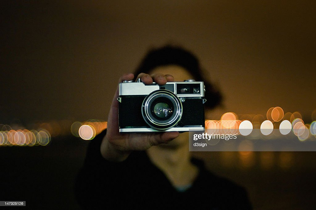 Man holding  camera at night : Stock Photo