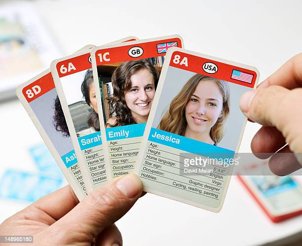 Man holding cards with various women's profiles