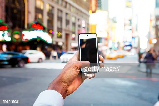 Man holding cellphone in Times Square