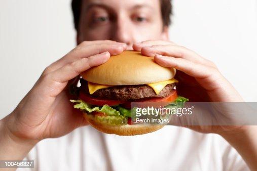 Man holding cheeseburger : ストックフォト