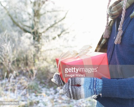 Man holding Christmas present in Winter setting. : Stock Photo