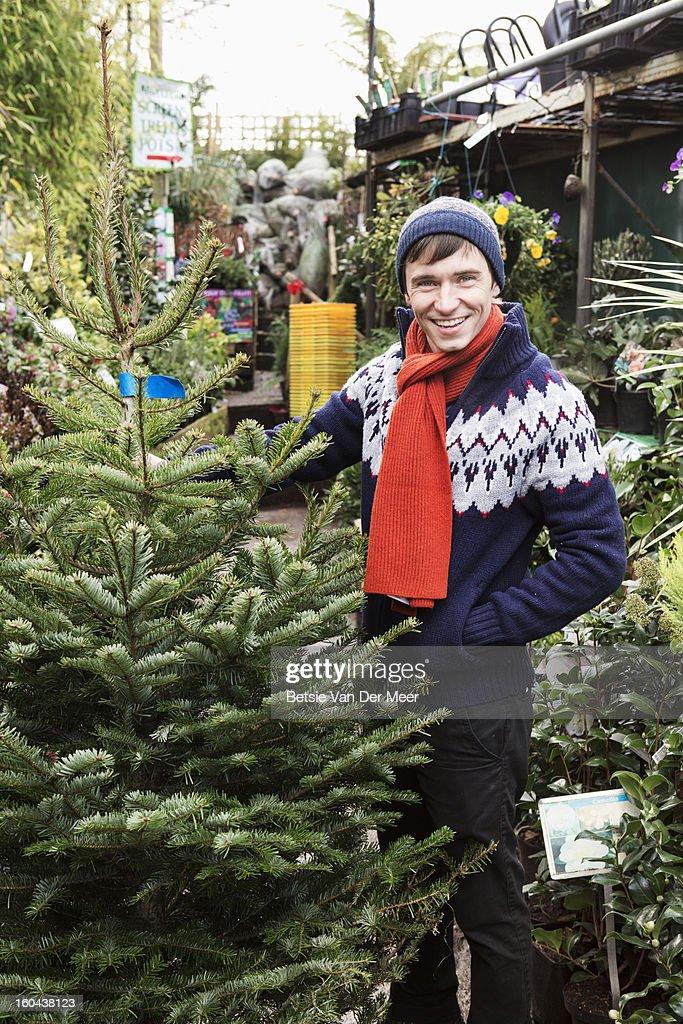 Man holding Christmas tree in garden centre. : Stock Photo